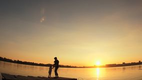 Silhouettes, a small child and woman standing on the pier by the water at sunset. Silhouettes, a small child and a woman, jumping and having fun on the pier on stock video footage