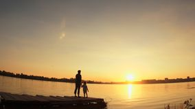 Silhouettes, a small child and woman standing on the pier by the water at sunset. Silhouettes, a small child and a woman, are on the pier on the background of stock video footage