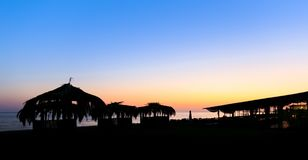 Silhouettes of small hovels with reed roofs and restaurant on the seashore at sunset Royalty Free Stock Photography
