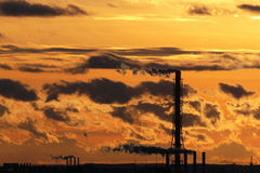 Silhouettes of smoking chimneys. Clouds at sunset in orange even Royalty Free Stock Photos