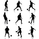 Silhouettes of soccer players with the ball. Royalty Free Stock Photography