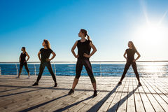 Silhouettes of sportive girls dancing near sea at sunrise. Stock Photos