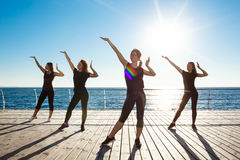 Silhouettes of sportive girls dancing near sea at sunrise. Stock Photography