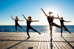 Silhouettes of sportive girls dancing near sea at sunrise. Royalty Free Stock Photo