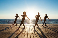 Silhouettes of sportive girls dancing zumba near sea at sunrise. Royalty Free Stock Image