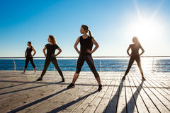 Silhouettes of sportive girls dancing zumba near sea at sunrise. Stock Photos