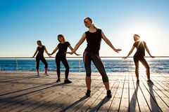 Silhouettes of sportive girls dancing zumba near sea at sunrise. Royalty Free Stock Photo