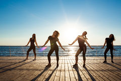 Silhouettes of sportive girls dancing zumba near sea at sunrise. Royalty Free Stock Images