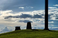 Silhouettes of stones and pillar with clouds at background. Silhouettes of stones and pillar on the grassy hill with clouds at background Stock Images