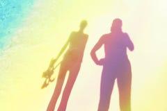 Silhouettes stylisées de femme tenant l'équipement et l'homme naviguants au schnorchel Photos stock