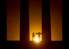 Silhouettes at sunrise. Two girls are enjoying the sunrise between two coloumns of the Athenian Acropolis on Calton Hill, Edinburgh Royalty Free Stock Photos