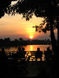Silhouettes at sunset. People in an outdoor cafe sitting at Mekhong silhouetted at sunset Stock Photography