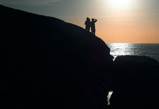 Silhouettes at sunset. Black silhouettes of a couple on the seashore rocks at sunset time Royalty Free Stock Images