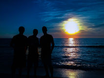 3 silhouettes with sunset in the background stock image