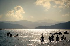 People bathing in the sea in Elba island, Toscana region, Italy. Silhouettes on a sunset beach in Italy royalty free stock images