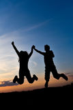 Silhouettes on the sunset. Boy and girl whirling on the sunset Stock Images