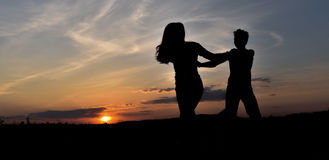 Silhouettes on the sunset. Boy and girl whirling on the sunset Royalty Free Stock Photo