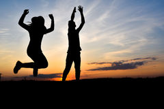 Silhouettes on the sunset. Boy and girl whirling on the sunset Royalty Free Stock Photos