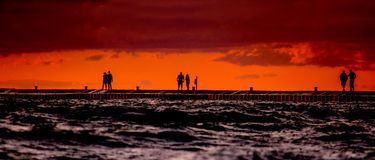 Silhouettes at sunset. Silhouettes of people stand out against a brilliant red sunset on lake michigan Royalty Free Stock Image