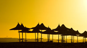Silhouettes of sunshades at sunset Royalty Free Stock Image