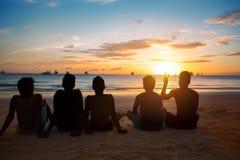 Silhouettes sur la plage au coucher du soleil Images stock