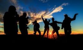 Silhouettes sur le coucher du soleil Image stock