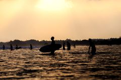 Silhouettes of surfers in the ocean at sunset stock image