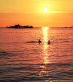 Silhouettes of a swimming couple and ship at sunset. Stock Photos