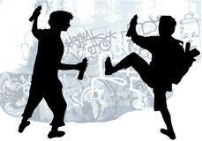 Silhouettes of taggers drawing graffiti. Two boys spray painting on the wall Stock Photos