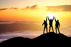Silhouettes of team. On mountain peak. Sport and active life concept Stock Photos