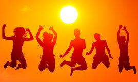 Silhouettes of teenage boys and girls jumping high in the air on. Sunny summer day royalty free stock images