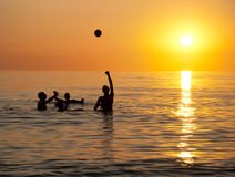Young people playing in ocean at sunset Royalty Free Stock Image