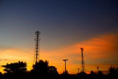 Silhouettes telecommunication tower and electric poles. Royalty Free Stock Image