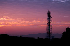 Silhouettes telecommunication tower at sunrise and twilight sky. Royalty Free Stock Photo