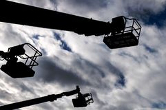 Silhouettes of three cranes against a blue cloudy sky royalty free stock photography