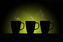Silhouettes of three cups on green background Stock Photography