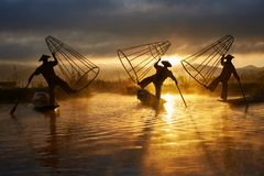 Silhouettes of three fishermen on Inle lake Myanmar. Silhouettes of three fishermen performance on Inle lake Myanmar at sunrise stock photography