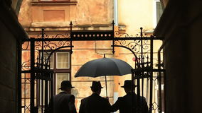 Silhouettes of three gentleman in a hats and vintage suits waiting near fancy metal door smoking and walk away