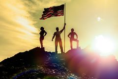 Silhouettes of three happy man on a mountain top, with flag america royalty free stock photography