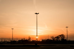 Silhouettes of three lampposts of street lighting form a perspective of a triangle against the sunset over the horizon Royalty Free Stock Image