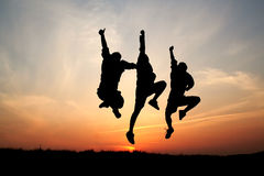 Silhouettes of three men jumping Royalty Free Stock Image