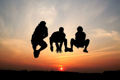 Silhouettes of three men jumping Royalty Free Stock Photo