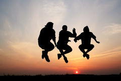Silhouettes of three men jumping Stock Images