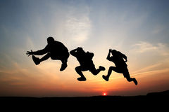 Silhouettes of three men jumping Stock Photo