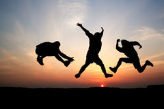 Silhouettes of three men jumping Royalty Free Stock Images