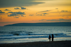 Silhouettes of three people walking on a beach a. T sunset, Bournemouth, UK, Europe Stock Photography
