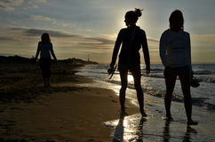 Silhouettes of three women going on the beach Stock Image