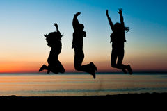 Silhouettes of three young friends jumping in the air at sunrise Royalty Free Stock Images