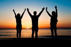 Silhouettes of three young friends throwing hands in the air Stock Photo