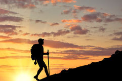 Silhouettes of tourist ascending the mountain at sunset Stock Photography